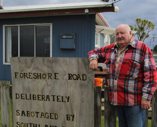 Kevin Mulqueen leans against a sign he attached to the fence of his Colac Bay home.