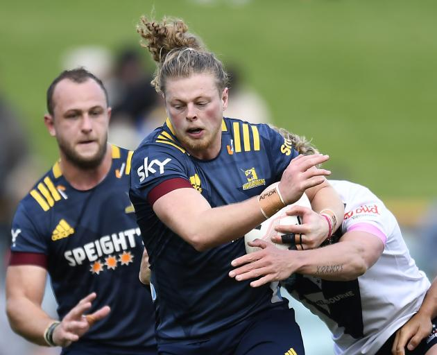 Highlanders midfield back Scott Gregory is supported by No8 Hugh Renton as he tries to break the...