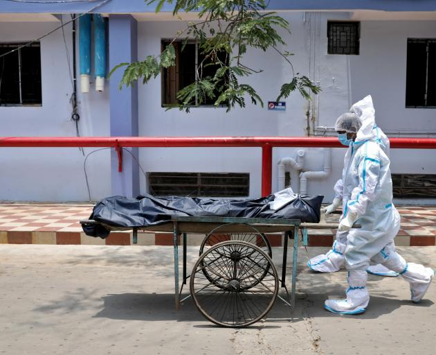 Healthcare workers transfer a body from a hospital in Kolkata on Wednesday. India accounts for...