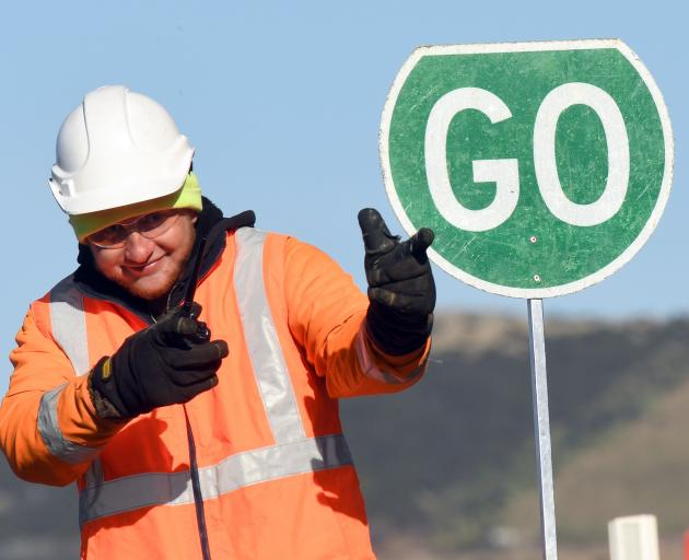 Downer Construction traffic controller Jarryd Osborne entertains waiting drivers with his moves...