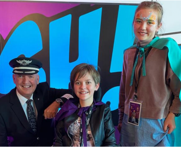 Air New Zealand chief pilot Captain David Morgan with Lilly, 12, and Annie, 11, before the flight...