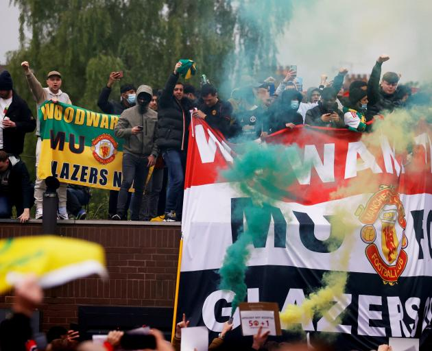 Manchester United fans protest against their American owners at Old Trafford on Sunday. Photo:...