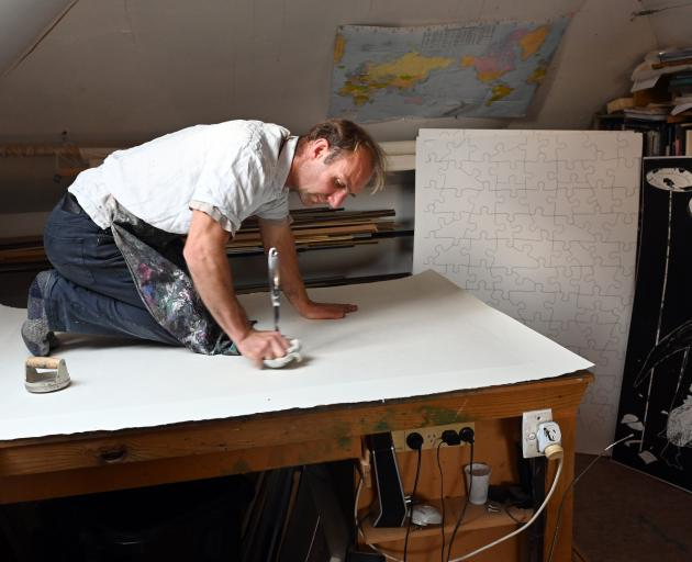 Manu Berry works on his penguin jigsaws for the Art + Science Project — ''Earth: Caught in Stone'...