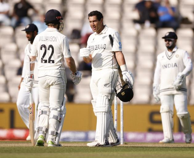 New Zealand's Ross Taylor reacts after getting hit on the helmet by a ball alongside Kane...