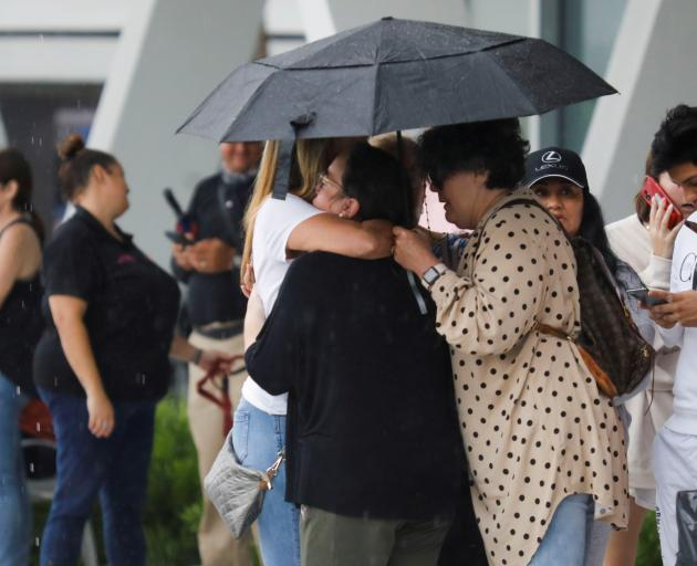 People embrace under an umbrella at the Surfside Community Center where authorities are taking...