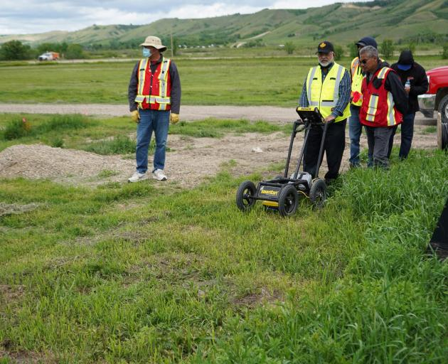 A crew performing a ground-penetrating radar search of a field, where the Cowessess First Nation...