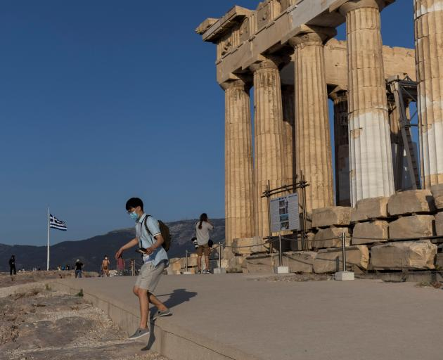 A man steps off the new cement walkway next to the Parthenon temple, built to improve access for...