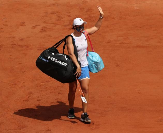 Ash Barty waves as she leaves the court injured during the French Open overnight. Photo: Getty...
