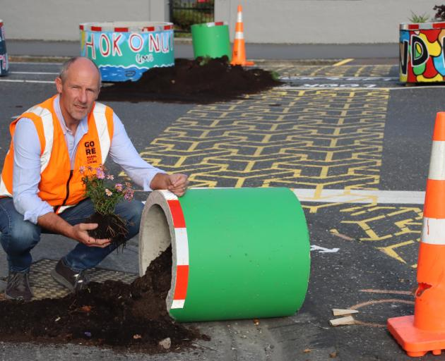 Gore District Council roading asset manager Peter Standring squats next to a vandalised planter...