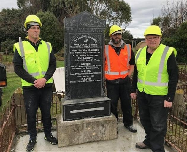 The headstone after repairs and installation were complete by Maiden Stone workers (from left)...