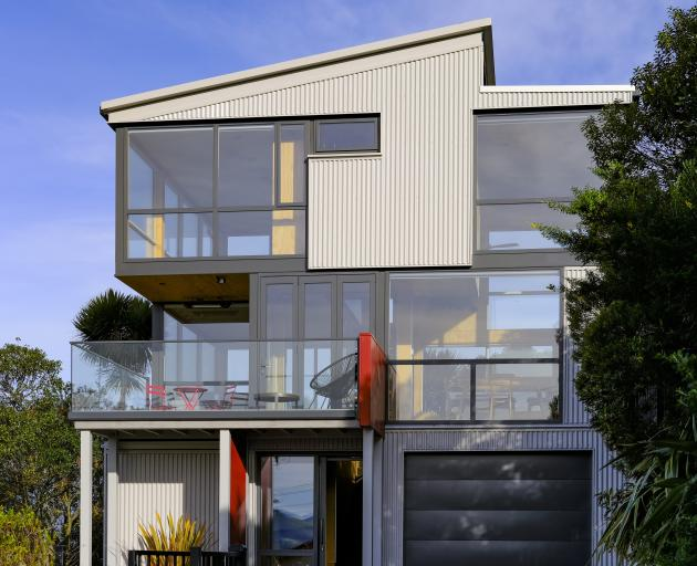 Grey cladding and window frames help the building blend in with its surroundings, while red...