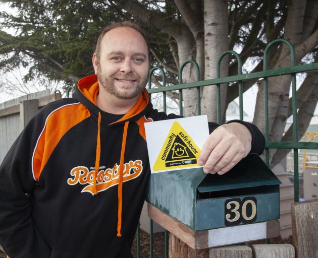 Grant Donnell with a Safe House Community Sticker. Photo: Geoff Sloan
