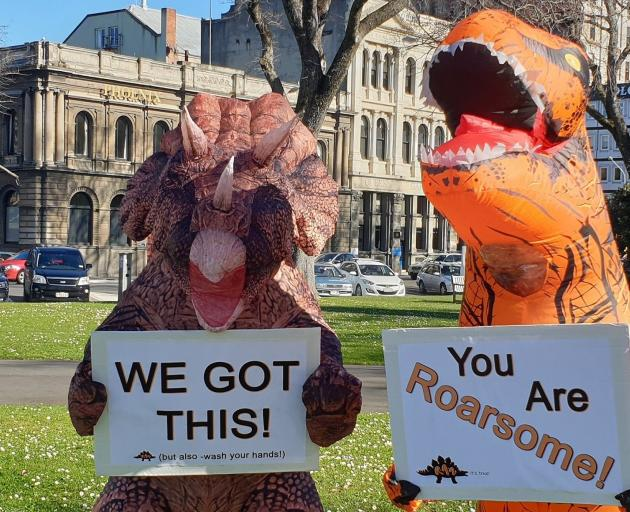 An inflatable dinosaur holds an encouraging sign  during a Random Acts of Art event. PHOTO: STAR...