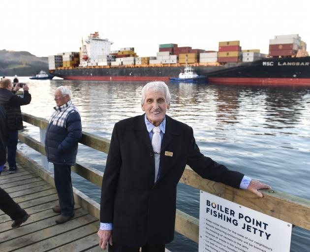 Warren Lewis stands on the jetty named after him as container ship MSC Langsar is guided past....