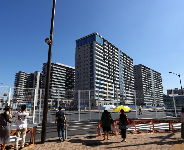 People stand next to fences as they take pictures of the athletes village in Tokyo. Photo: Reuters