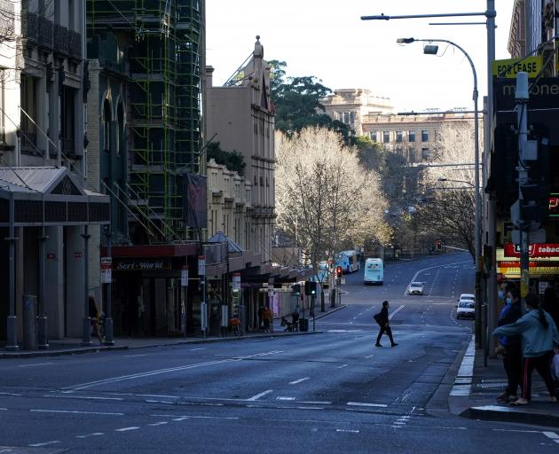 A pedestrian crosses an almost empty street in the centre of Sydney, which is in lockdown until at least July 30. Photo: Reuters