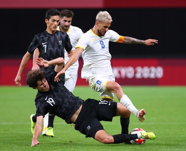 Olywhite Matthew Garbett makes a play for the ball with Marius Marin of Romania. Photo: REUTERS