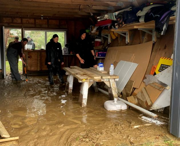 Students clean the inside of a resident's garage after it flooded. CREDIT: OUTWARD BOUND/SUPPLIED