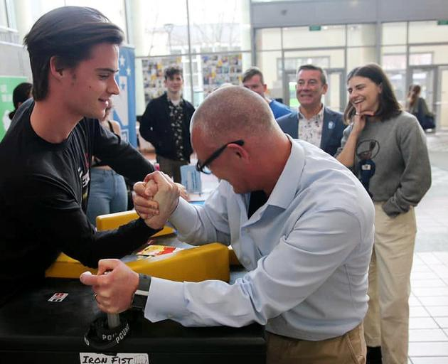 Labour MP David Clark takes part in an arm-wrestling competition with an unknown student in the...