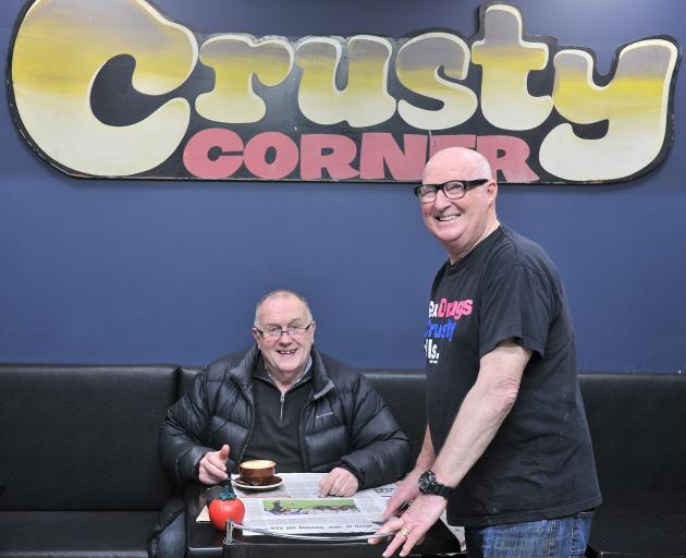 Crusty Corner owner Rob Barker (standing) serves regular customer Geoff Oswald yesterday. PHOTO:...