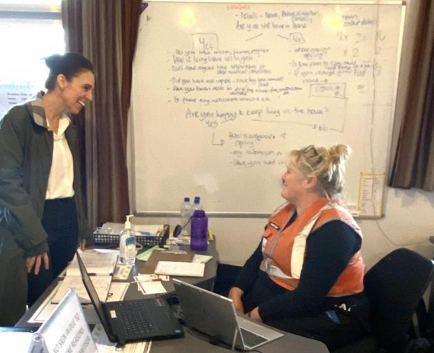 Prime Minister Jacinda Ardern (left) speaks with a volunteer at the Buller Emergency Management...