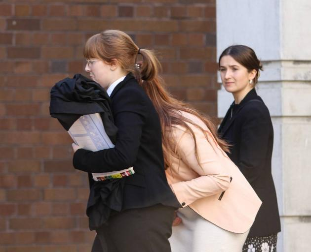 Kathy Stephens (in the pink jacket) hides behind her lawyer Christina Hallaway outside the High Court at Auckland last week. Photo / NZ Herald