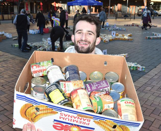 Volunteer George Blake with a selection of cans given to the appeal. Photo: Gregor Richardson