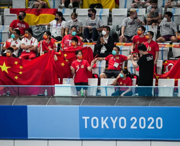 Members of the Chinese delegation support athletes during the Men's 10 metre Synchronized Platform Diving Final. Photo: Getty Images
