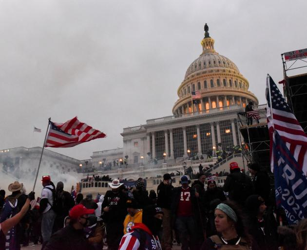 Police tried to clear the US Capitol Building with tear gas as supporters of President Donald...