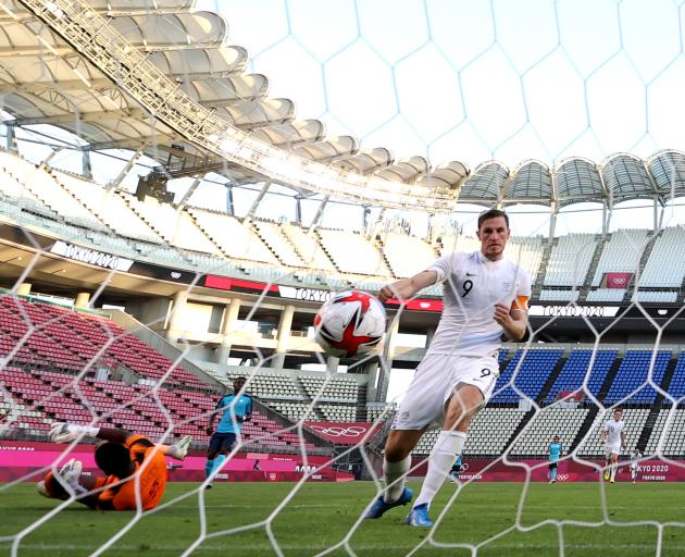 Burnley striker Chris Wood scores for the OlyWhites during his side's group B match against...