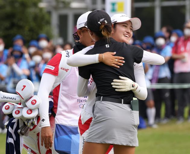 Lydia Ko (in black) embraces Mone Inami after the tense playoff for silver in Tokyo. Photo: Getty...