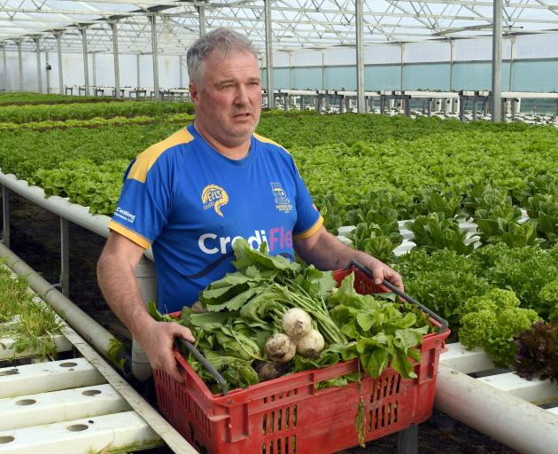 Carrying a crate full of vegetables is Janefield Paeonies and Hydroponics owner Rodger Whitson,...