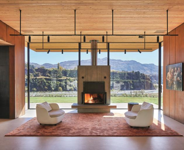 The concrete fireplace appears to float within a large wall of glass. PHOTOS: STUDIO JUBB AND...
