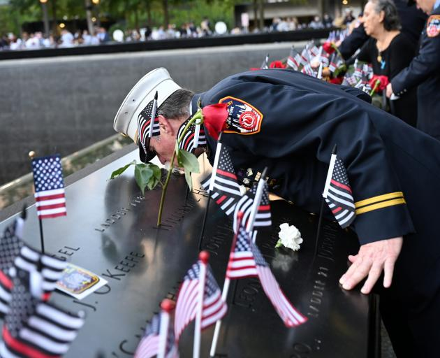 Retired Paramedic Chief Charlie Wells kisses the name of a relative killed in the attack on the...