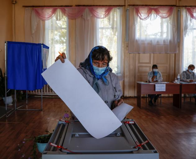 A woman wearing a protective face mask casts a ballot at a polling station during a three-day...