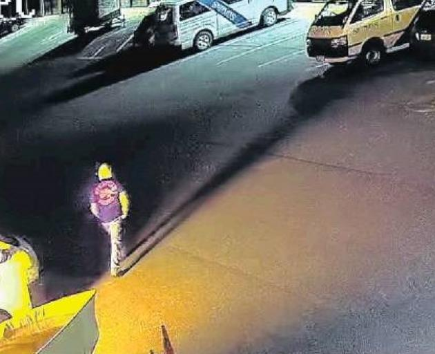 The fire illuminates his clothing as he walks away, the back of his T-shirt showing a printed insignia of the Red Devils motorcycle gang. Photo: Supplied