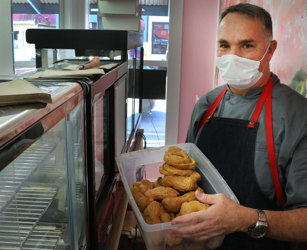 Lawrence's La Boulangerie barista Deon Vosloo restocks the cabinets at the very popular bakery. PHOTO: JOHN COSGROVE