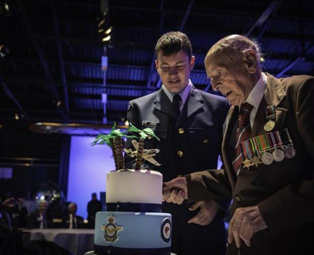 Ron Hermanns cutting the cake at his 108th birthday with help from the youngest serving airman in...