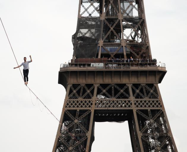 French acrobat Nathan Paulin walks on a slackline between the Eiffel Tower and the Theatre National de Chaillot as part of events around France for National Heritage Day in Paris. Photo: Reuters