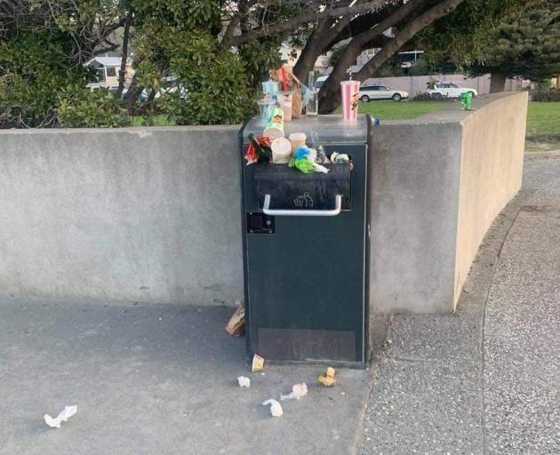 An overflowing rubbish bin in Sumner. Photo: Supplied