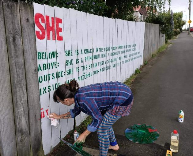 Iona Winter puts the finishing touches on her poem ''Her'' on a Port Chalmers fence. PHOTO: SUPPLIED