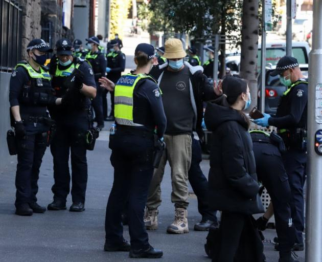 Police search a man ahead of a planned protest in Melbourne on Thursday. Photo: Getty Images