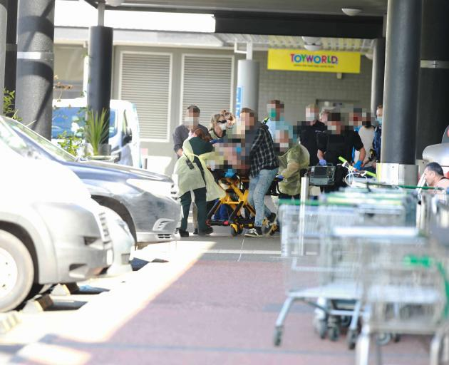 Emergency services rush an injured person to an ambulance. Photo: NZ Herald