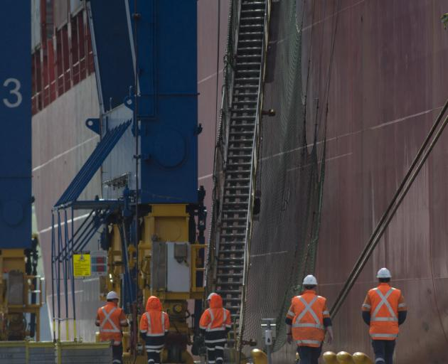Port Otago workers beside the container ship Rio de Janeiro at Port Chalmers yesterday. All the...