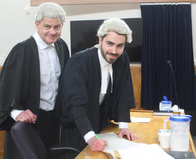 Lawyer Malcolm McKenzie swears in his son, William, as a barrister and solicitor in the High...