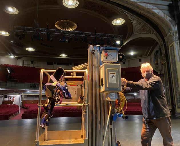 Regent Theatre technical manager Nelson Miles positions an elevated working platform on the stage...