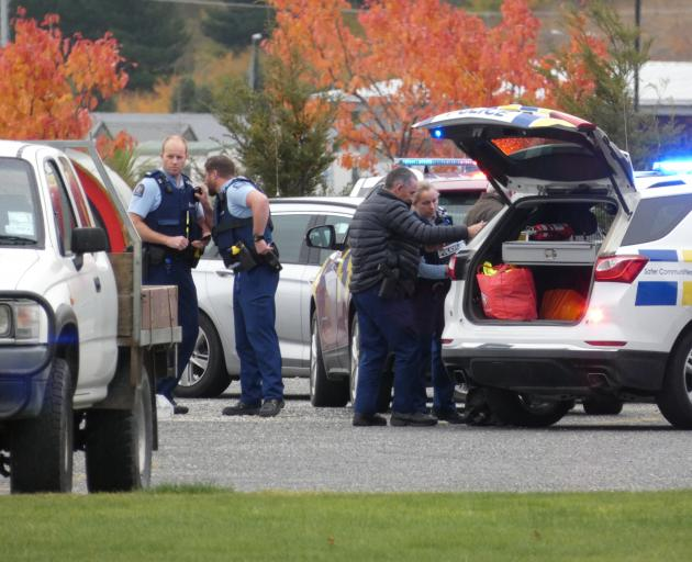Police officers escort a 59-year-old man (obscured) wanted in relation to family harm and...