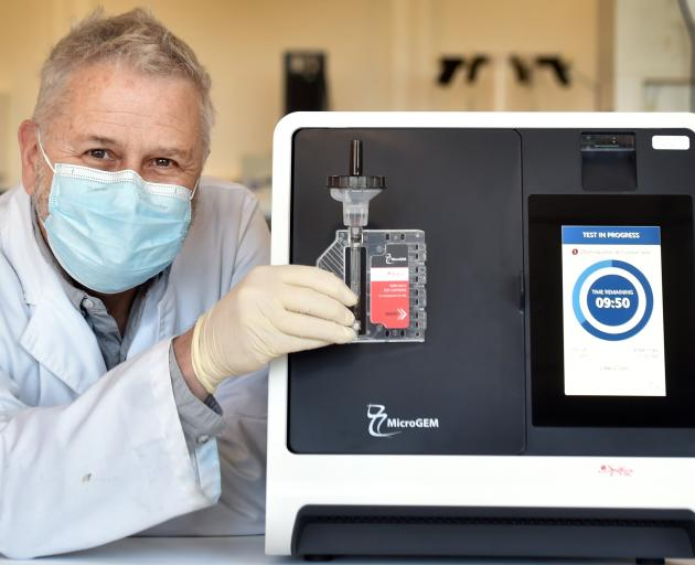 MicroGEM chief scientific officer Dr David Saul shows the Covid-19 saliva test which the business...