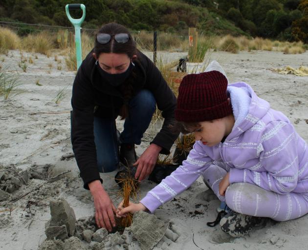 Okahau dune project organiser Angelina Young helps Warrington School pupil Skyla Bussell (14)...