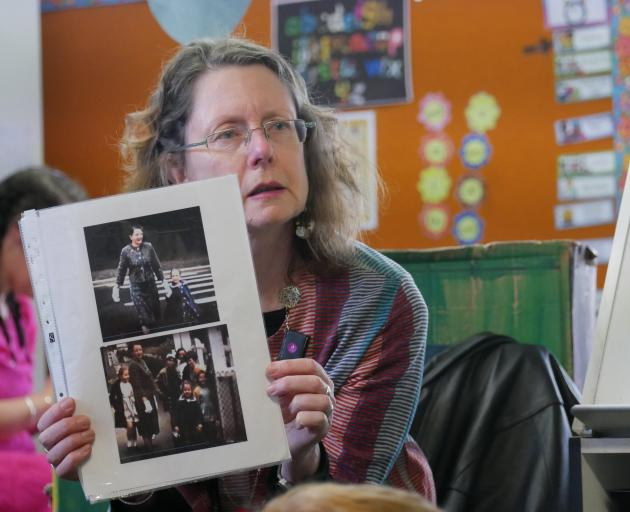 Poet Jenny Powell shows Tainui School pupils photographs of her first day at the school as a...